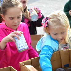 Two girls from the Father-Child YMCA day at Mission Arlington help to sort Thanksgiving food.