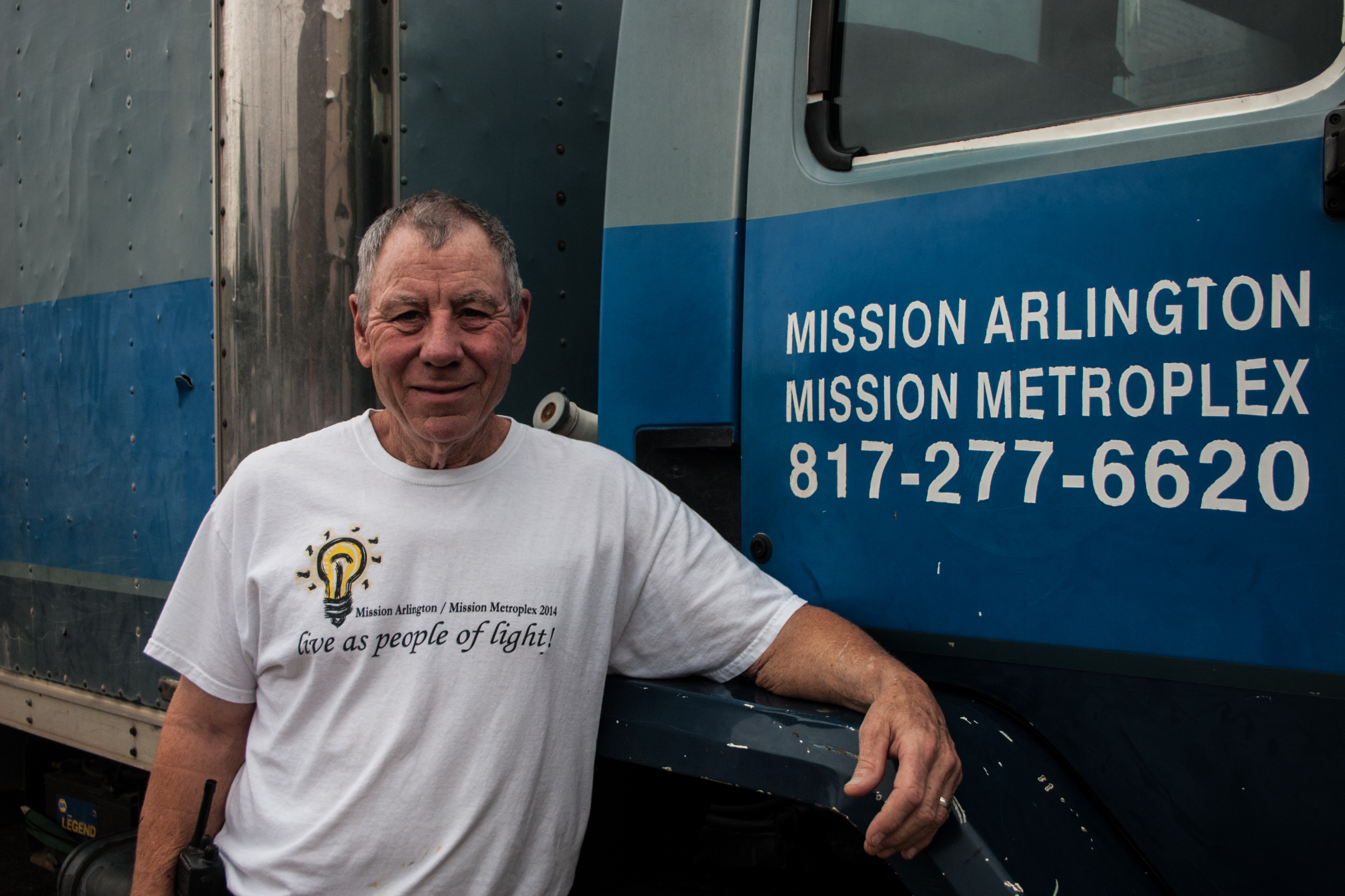 "Tommy, standing by the ""Blue Box,"" the Mission Arlington truck he drives to pick up and deliver furniture."
