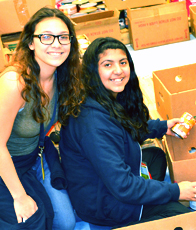 Two students from Arlington Collegiate High School help sort food in preparation for Thanksgiving.